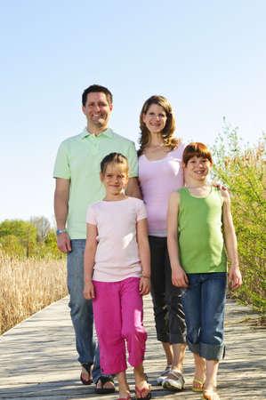 Portrait of happy family of four walking on boardwalk Stock Photo - 5021022