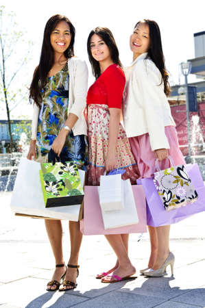 Group of young girl friends holding shopping bags at mall photo