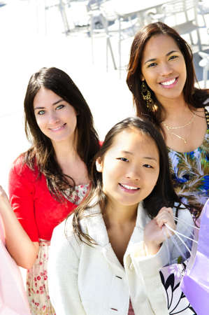 Three young girl friends holding shopping bags at mall Stock Photo - 5021023