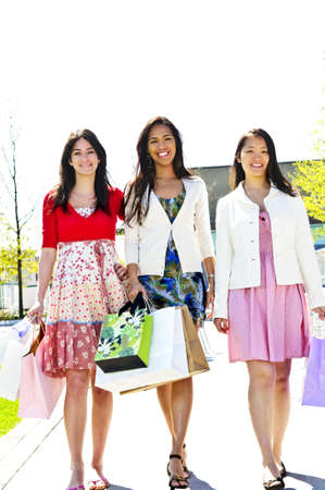 Three young girl friends holding shopping bags at mall Stock Photo - 5021013