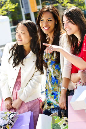 Three young girlfriends at outdoor mall pointing photo