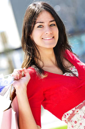 Portrait of young woman with shopping bags at outdoor mall photo