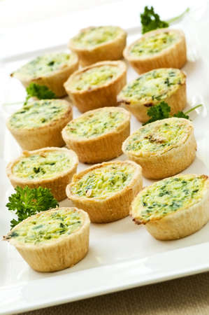 Plate of many mini bite size quiche appetizers photo