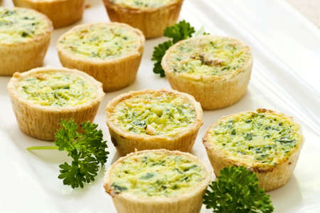 caterer: Plate of many mini bite size quiche appetizers