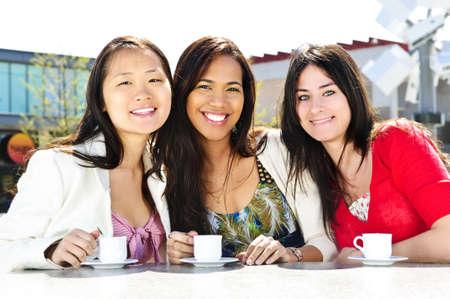 座っているとの屋外カフェで飲み物を持つ少女の友人のグループ 写真素材