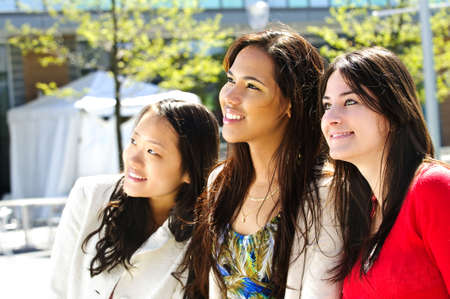 Three diverse young girlfriends smiling into camera photo
