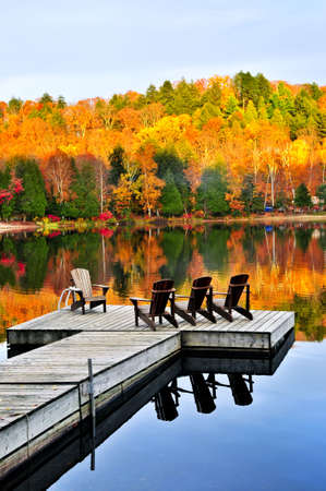 Wooden dock with chairs on calm fall lake Stock Photo - 5101568