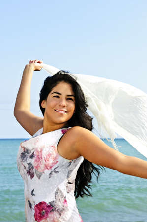 Portrait of beautiful smiling brunette girl at beach holding white scarf photo