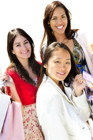 Three young girl friends holding shopping bags at mall photo