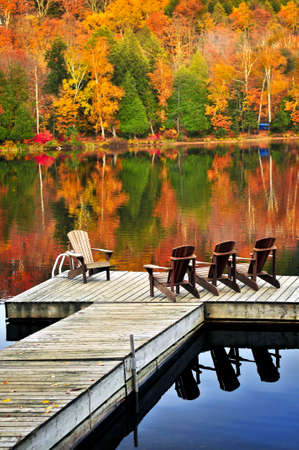 Wooden dock with chairs on calm fall lake photo