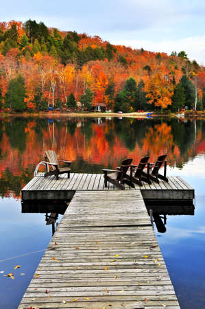 adirondack chair: Wooden dock with chairs on calm fall lake