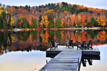 Quai en bois avec des chaises sur le lac calme automne