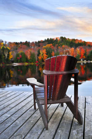 Wooden dock with chair on calm fall lake photo