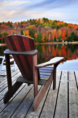 adirondack chair: Wooden dock with chair on calm fall lake