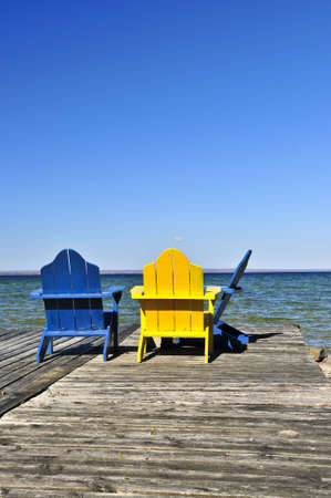 Painted wooden chairs on dock at a lake photo