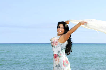Portrait of beautiful smiling brunette girl at beach with arms outstretched photo