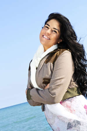 indian ocean: Portrait of beautiful smiling brunette girl at cool windy beach Stock Photo
