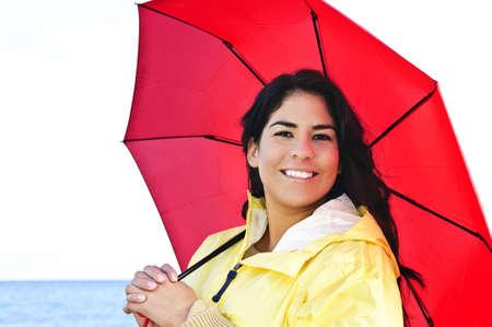 Portrait of beautiful smiling brunette girl wearing yellow raincoat holding red umbrella photo
