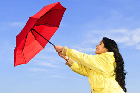 gusty: Portrait of beautiful girl wearing yellow raincoat holding red umbrella on windy day