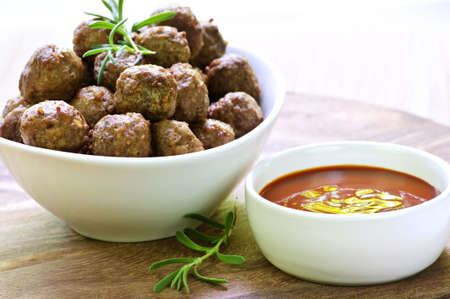 heaping: Fresh hot meatball appetizers served in white bowl with dipping sauce