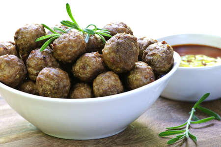 Fresh hot meatball appetizers served in white bowl with dipping sauce