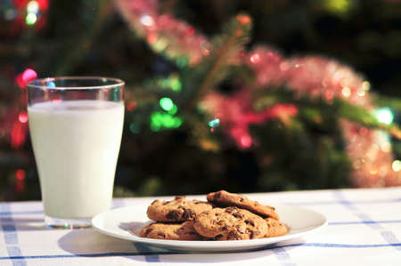 Plate of cookies and glass of milk near Christmas tree photo