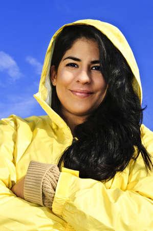 Portrait of beautiful smiling brunette girl wearing yellow raincoat against blue sky photo