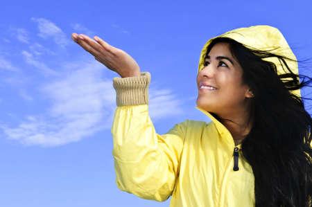slicker: Portrait of beautiful smiling girl wearing yellow raincoat looking up checking for rain Stock Photo