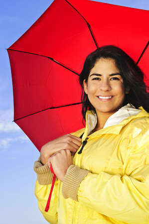 Portrait of beautiful smiling brunette girl wearing yellow raincoat holding red umbrella photo