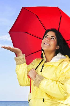 Portrait of beautiful smiling girl wearing yellow raincoat holding red umbrella checking for rain Stock Photo - 5205226