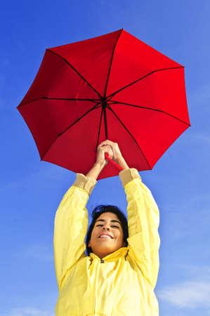 Portrait of beautiful girl wearing yellow raincoat holding red umbrella on windy day photo