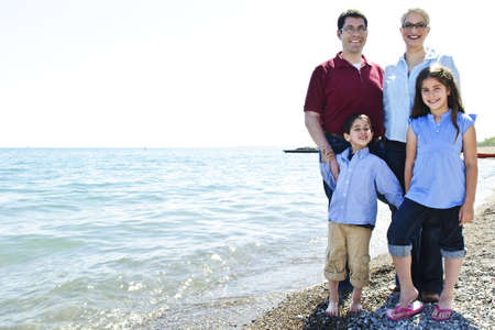 Happy family standing on shore at the beach photo