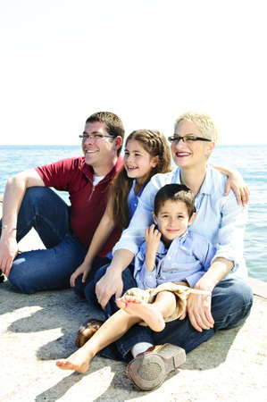 Happy family sitting on pier at lake photo