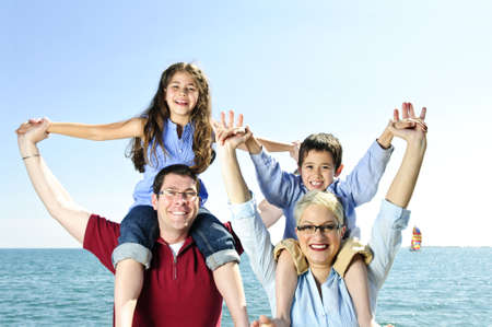 Happy family having fun giving shoulder rides photo