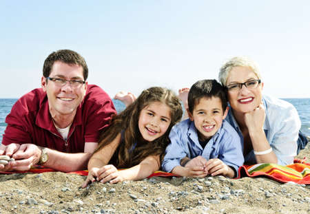 glasses in the sand: Happy family laying on towel at sandy beach