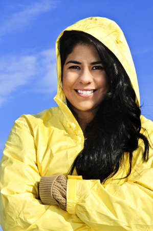 aboriginal woman: Portrait of beautiful smiling brunette girl wearing yellow raincoat against blue sky Stock Photo