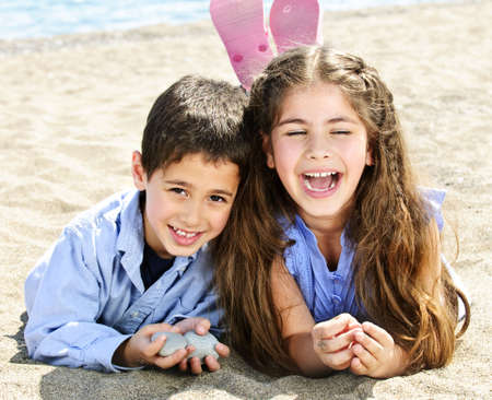 Portrait of brother and sister laying on sand at the beach photo