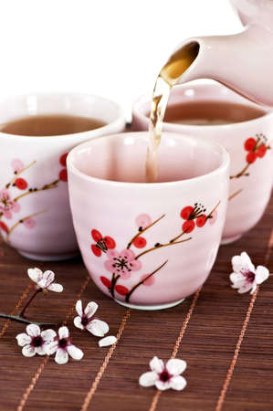Pouring green tea into cups with cherry blossom design photo