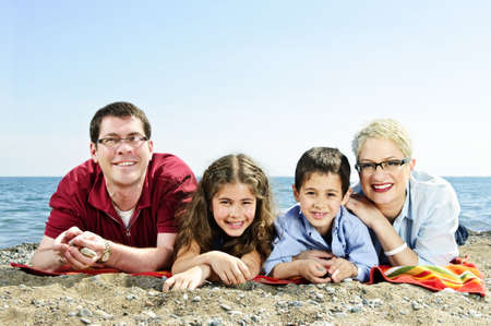 Happy family laying on towel at sandy beach photo