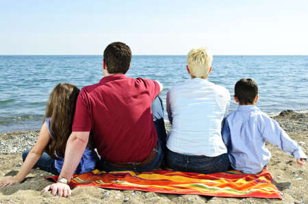 Family sitting on towel at sandy beach photo