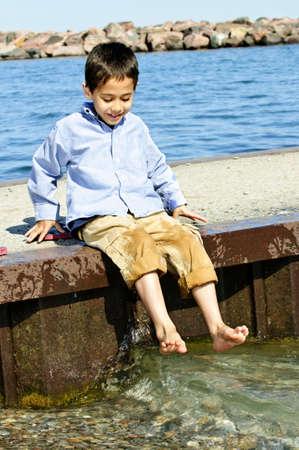 Portret van jonge jongen dompelen voeten in het meer van pier