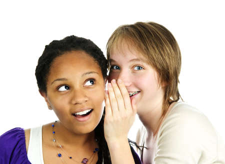 Isolated portrait of two diverse teenage girl friends whispering photo