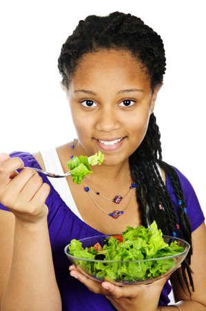 Isolated portrait of black teenage girl with salad bowl photo