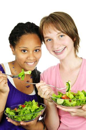 Geïsoleerde portret van twee tienermeisjes eten salade Stockfoto