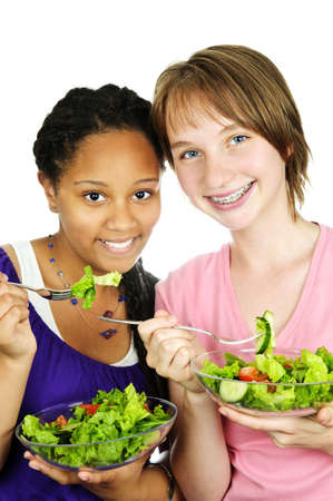 Isolated portrait of two teenage girls eating salad