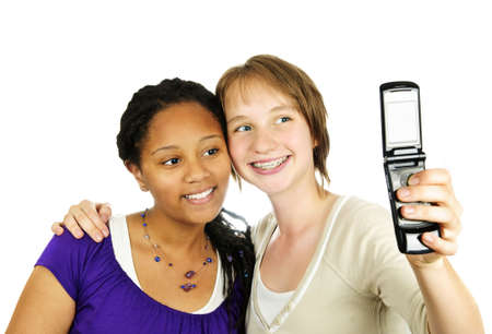 Isolated portrait of two teenage girls with camera phone photo