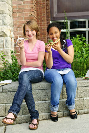eating: Two teenage girls sitting and eating pizza
