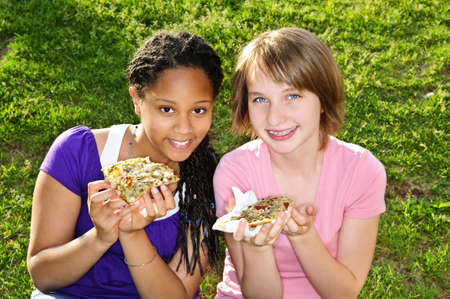 Two teenage girls sitting and eating pizza photo