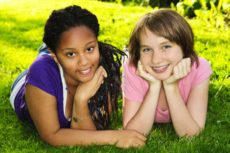 Two happy teenage girls laying on grass photo