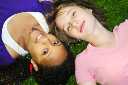 Two teenage girls laying on grass looking up photo